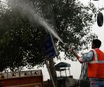 NDMC workers sprinkle water on tree, streets to curb pollution