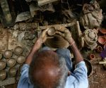 : New Delhi:A potter carries earthen lamps to dry ahead of Diwali festival.