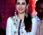 Happy, smiling Karisma sips coffee as she looks glam in simple ethnic outfit