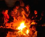 People warm themselves around a fire