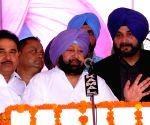 :Amritsar: Punjab Chief Minister Captain Amarinder Singh addresses during the foundation stone laying ceremony for various development projects along with state cabinet ministers Navjot Singh Sidhu ...(Image Source: IANS)
