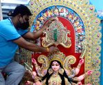 Artist Kaushik Ghosh gives finishing touches to a 4 foot fiberglass idol of Goddess Durga which will go to Italy by ship, at the Kumartoli workshop in Kolkata.