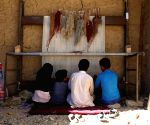 Afghan children weave carpet