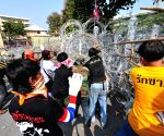 Thai anti-government protestors remove barbed wire barriers outside the courtyard of Government House