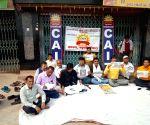 Free Photo: Patna: CAIT members sitting on dharna at a market at Madhubani in Darbhanga district during Bharat Bandh