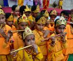 Children dressed as Lord Krishna take part in a school function