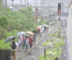 Commuters walk on railway tracks