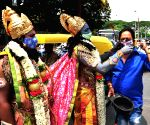 Devotees dressed like Lord Sri Rama and Lord Hanuman distribute face masks during the Coronavirus Pandemic, on the eve of Sri Ramanavami Festival near Anand Rao Circle, in Bengaluru on Wednesday 21st April 2021