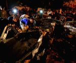 Palestinians gather around the remains of the car which police said was targeted in an Israeli airstrike