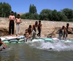 Afghan children cool themselves in a canal
