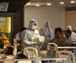 : Health workers wearing PPE suits and treatment for COVID-19 positive patient admit in Emergency Covid-19 care center by Delhi Government at Shahnai banquet Hall in front of LNJP hospital in New Delhi on Wednesday April 21, 2021