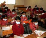Children wear masks  to avoid contracting swine flu