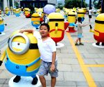 A boy plays around among minions figures in Jinan, capital of east China's Shandong Province