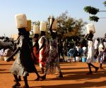 South Sudanese people walk in a UN camp in Juba