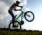 Kolkata : A boy is doing a bicycle stunt at Maidan in Kolkata