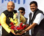 Amit Shah hands over a cheque to kin of political clash victims