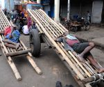 Labourers resting outside wholesale market amid protests during nationwide trade union strike