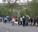Large numbers of migrants going by pedestrian for their native place, after lockdown announcement in National Capital in the wake of rising Covid-19 cases, in New Delhi