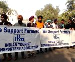 Members of Indian Tourist Transporters Association stand in support of farmers at Vigyan Bhawan