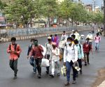 Migrants walk pass to reach their native palaces, amid a total lockdown imposed to curb the spread of COVID-19, in Patna, Wednesday, May 12, 2021