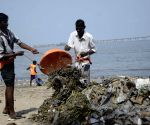 Workers clean sea beach on the eve of World Environment Day
