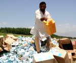 An Afghan man pours petrol over expired medicine and food