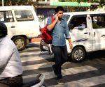 A man speaks over phone as he crosses road