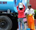 People collect water from a tanker