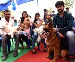 Participants hold their pets during a Dog Show competition at Bihar Veterinary college in Patna