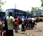 Passengers stand in a queue at a bus stand waiting for the bus during the suspension of local train services across the State in view of the coronavirus disease (Covid-19) situation in Kolkata .
