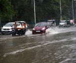 BCommuters wade through the waterlogged road in Patna.