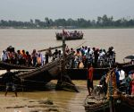 People along with their vehicle travel by boat to cross the flooded Ganga River, at Kachchi Dargah in Patna