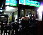 People queue up outside an ATM