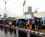 People stand in a queue for vaccination in the rain at Kishore Bharati Stadium during the coronavirus pandemic in Kolkata