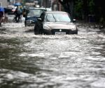 People wade through a waterlogged road during heavy rain in Kolkata.