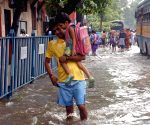 People wade through water logged roads