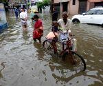 People wade through a waterlogged street at Ekbalpur area during heavy rainfall in Kolkata.