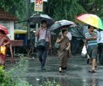 People walking during heavy rain in Kolkata