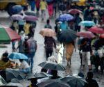 People walking on the road holding umbrella during heavy rain in Kolkata.
