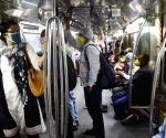People wear face masks and face shields while travelling in the metro amid COVID-19