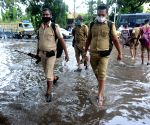 Police personnel waded through a water logged street during rainfall in Kolkata.