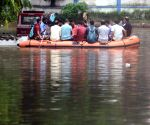 Police personnel with their family members are crossing the waterlogged area by boat at Alipore Body Guard Lines during rainfall in Kolkata.