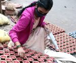 :Kolkata: Potters painting earthen lamps for the upcoming Diwali festival at Pottery Town in Bangalore