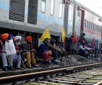 Protesters sit on rail tr