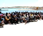 Qara Bolle: Some illegal immigrants sit on the ground after being rescued off the coast of Qara Bolle, in Libya
