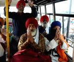 Sikh pilgrims wave from a bus before leaving for Pakistan for Baisakhi celebrations, in Amritsar