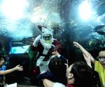 A diver dressed as Santa Claus interacts with children and volunteers from the Society for the Physically Disabled
