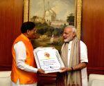 """PM Modi recieves a copy of the book - """"Narendra Modi: The Making of A Legend"""