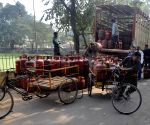 Workers unloading LPG cylinder from a truck