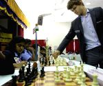 World Chess Champ Magnus Carlsen making a move playing with 20 young chess players